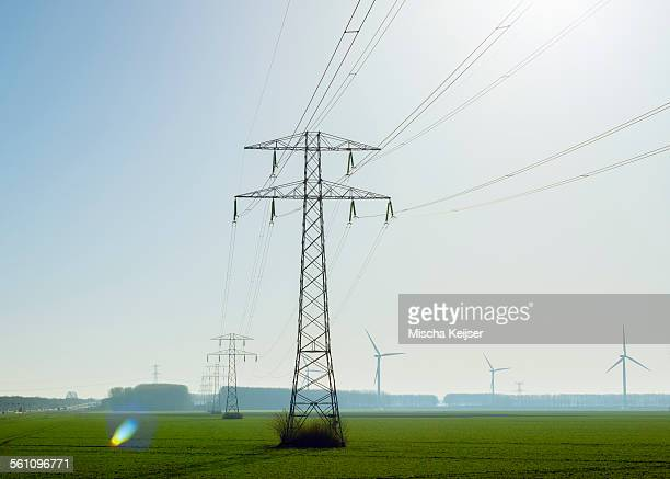 Electric pylons in front of row of wind turbines, Riland, Zealand, Netherlands