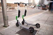 An electric scooter parked in the middle of a city street. Madrid, Spain