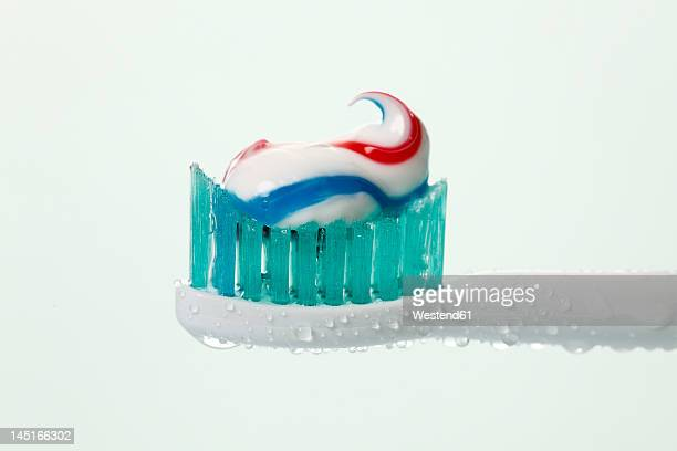 Electric toothbrush with toothpaste against white background, close up
