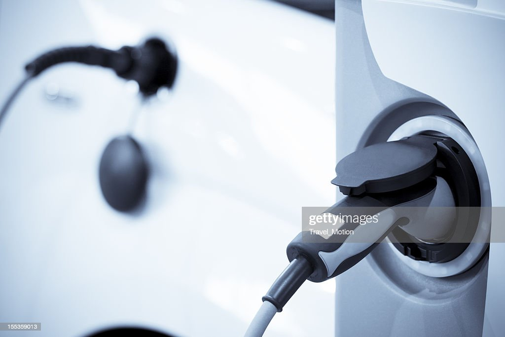 Electric vehicle charging, focus on foreground : Stock Photo