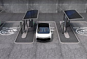 Electric vehicle charging station in public space. The charging spot support by solar panels, storage batteries. 3D rendering image.