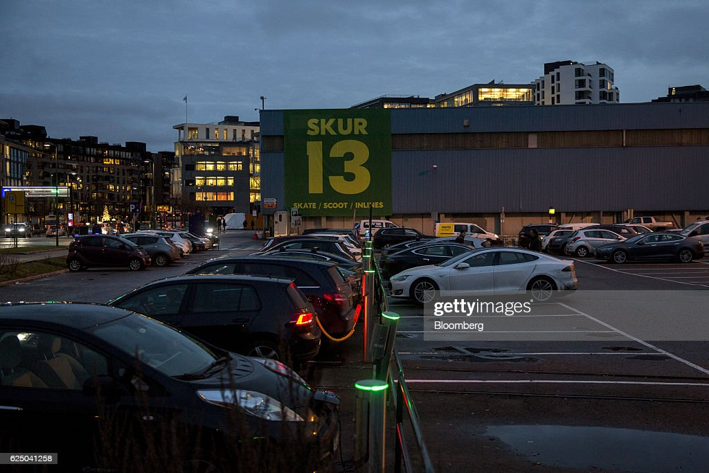 Electric vehicles (EV) sit parked at illuminated charging stations outside a skatepark near the financial district in Oslo, Norway, on Monday, Nov. 21, 2016. The International Energy Agency forecasts that global gasoline consumption has all but peaked as more efficient cars and the advent of electric vehicles from new players such as Tesla Motors Inc. halt demand growth in the next 25 years. Photographer: Fredrik Bjerknes/Bloomberg via Getty Images