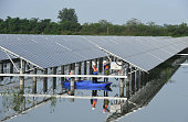 Electric workers check solar panels and generating devices by boat at Mumahu Village of Tianchang City on July 13 2016 in Chuzhou Anhui Province of...