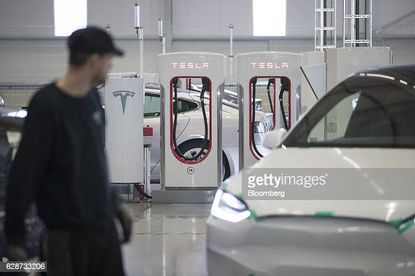 Electrical charging stations stand on the factory floor at the Tesla Motors Inc electric automobile factory in Tilburg Netherlands on Friday Dec 9...