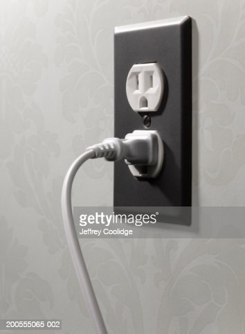 Electrical cord plugged into wall outlet, close-up