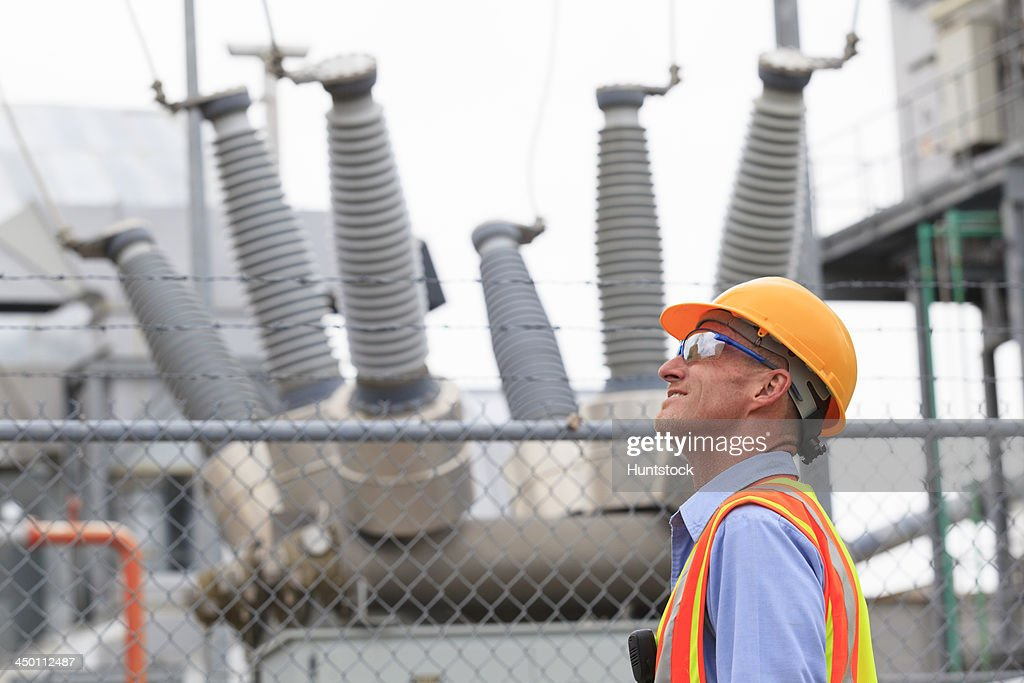 Electrical engineer examining transformers inside of an electric power plant