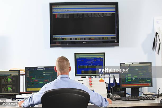 Electrical engineer in central operating command room at power station using monitors to track performance