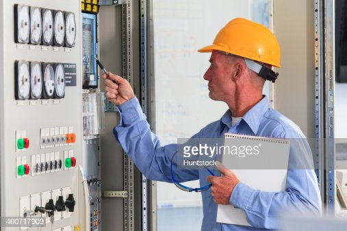 electrical engineer inspecting power plant controls in central operations room of power plant stock photo - Power Plant Engineer