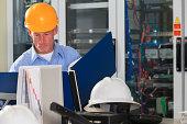 Electrical engineer reviewing data logs in broadband communication hub