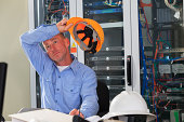 Electrical engineer taking a break from reviewing data logs in broadband communication hub