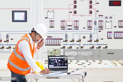 Electrical engineer working at control room of thermal power plant : Stock Photo