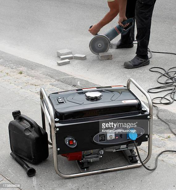 Electrical generator in foreground and man using masonry saw
