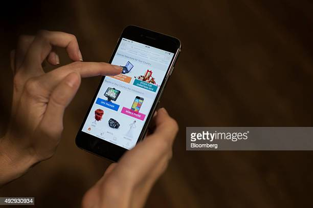 Electrical goods are displayed on Alibaba Group Holding Ltd's smartphone shopping app as a user holds a smartphone in this arranged photograph in...