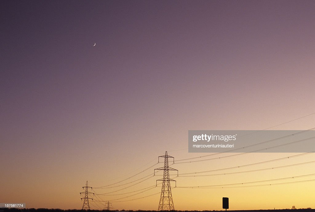 Electrical Moon - Electricity pylons in a sunset sky : Stock Photo