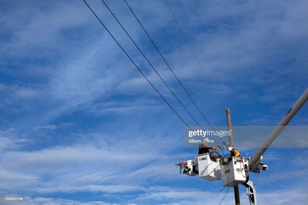 Electrical repair workers try to fix a telephone pole that was brought down by last nights storm November 8, 2012 in Long Branch, New Jersey. The storm brought gusting winds, rain, snow and forced the cancelation of thousands of passengers flying out of JFK, LaGuardia and Newark.