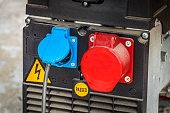 Blue and red electric sockets in the power generator closeup