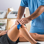 Electrical stimulation in physical therapy. Therapist positioning electrodes on a patient's knee
