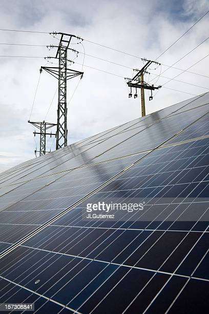 Electrical towers behind energy grid panels with sky