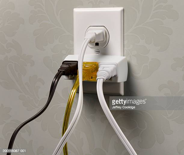 Electrical wall outlet overloaded with plugs, close-up