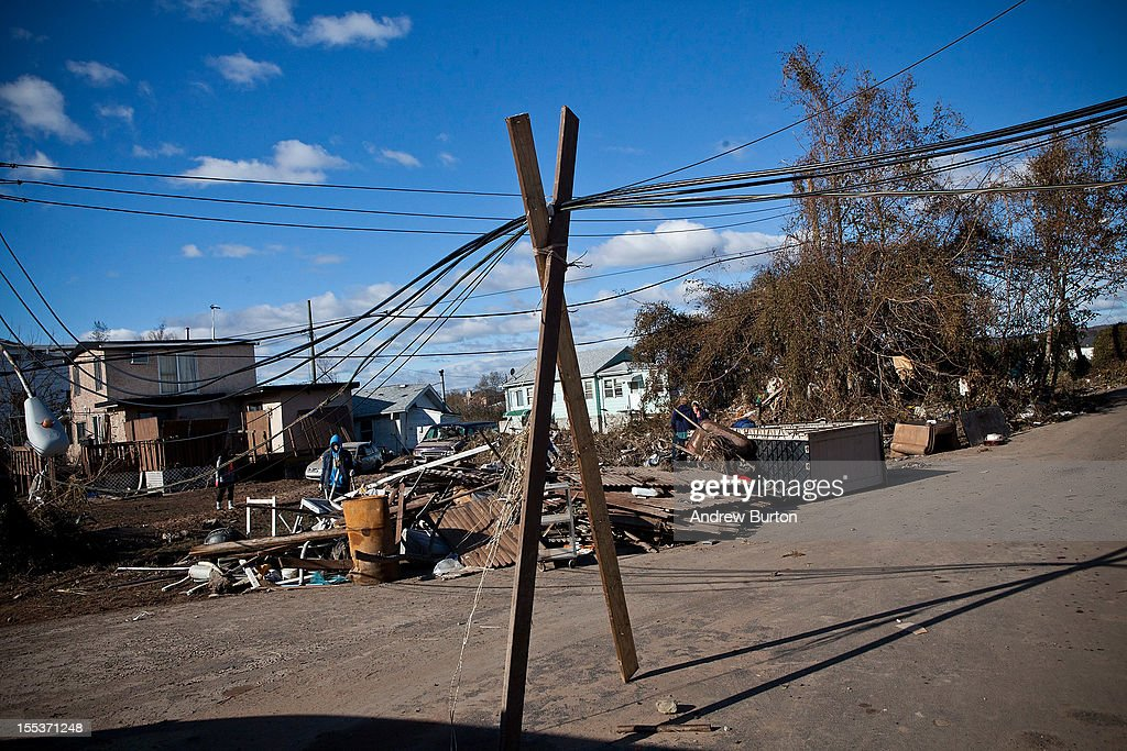 Electrical wires are precariously balanced on top of two beams in the Midland Beach neighborhood of Staten Island on November 3, 2012 in New York City. As clean up efforts from Superstorm Sandy continue, colder weather and another storm predicted for next week are beginning to make some worried.