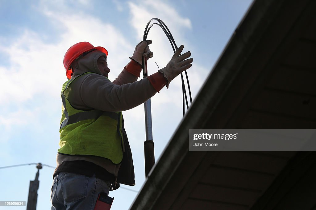 Electrical workers restore power to a house damaged by Superstorm Sandy on January 4, 2013 in the New Dorp area of the Staten Island borough of New York City. More than two months after the storm, Congress passed legislation today that will provide $9.7 billion to cover insurance claims filed by people whose homes were damaged or destroyed by Sandy.