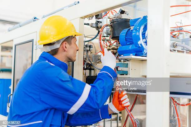 Electrician checking wires and cables on machine in factory