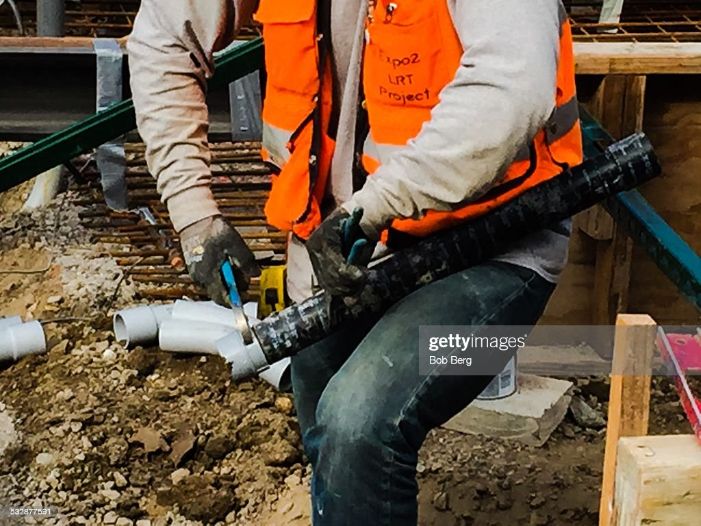Santa Monica Ca January 8 2015 A electrician construction worker uses a wrench and his body to tighten an electrical fitting onto a pipe fitting