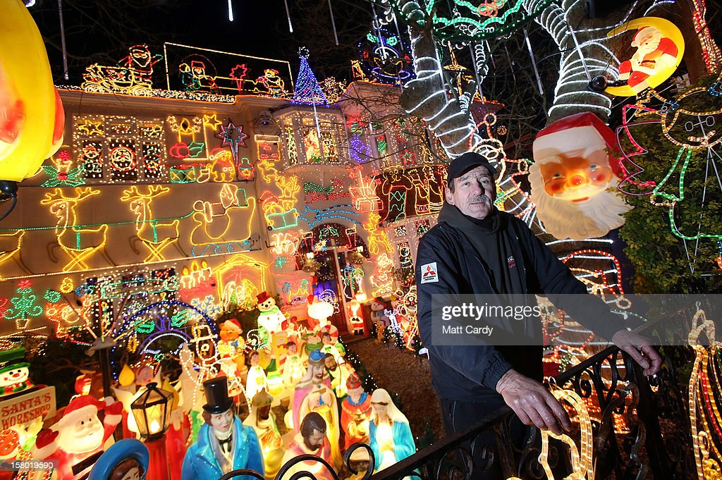 Electrician Graham Fryer poses besides the Christmas festive lights that he helped fit to a detached house in a suburban street in Melksham, December 8, 2012 in Melksham, England. The lights, a popular festive attraction, have returned to the town after a two-year absence and have raised thousands of pounds for charity for a local hospice, Dorothy House. The display, which is estimated to involve over 100,000 bulbs, worth over 30,000 GBP and even needed an up-rated electricity supply installed to cope with the additional power needed, is the brainchild of householder and electrician Alex Goodhind. This year, the display which Mr Goodhind began fifteen years ago now takes a team of professional electricians five weeks to complete, and even includes a snow machine.