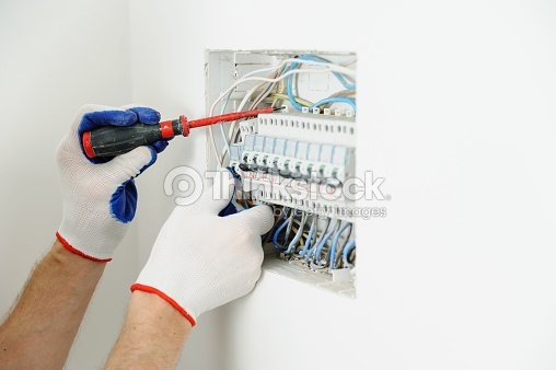 electrician installing an electrical fuse box   : stock photo