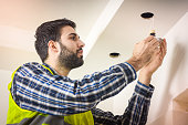 Young electrician in checkered shirt installing light bulb