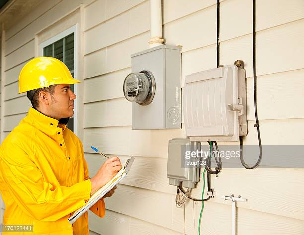 Electrician, repairman at outside electric meter on home. Yellow raincoat.