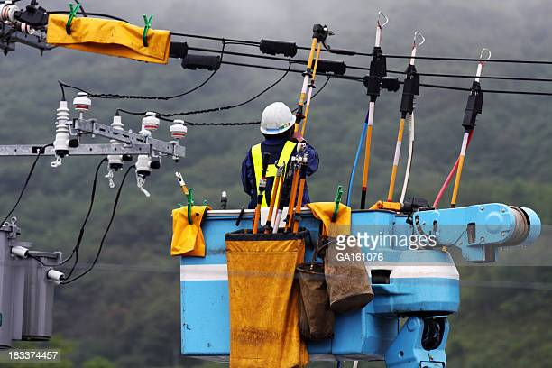 Electrician repairs a power line under the falling rain