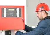Young attractive electrical engineer at work with a red helmet on his head
