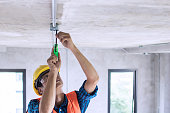 Electrician wiring on ceiling in construction site