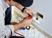 Electrician stripping the cable to connect switches and sockets of a residential electrical installation