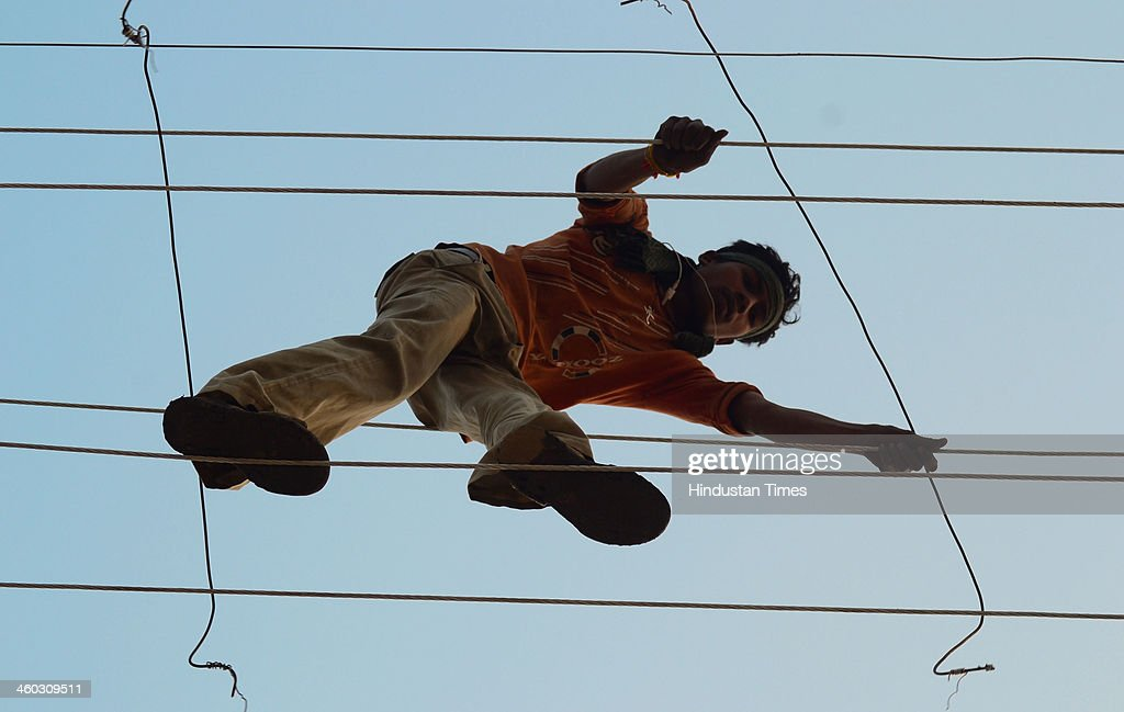 Electrician working on the temporary electric cables on the banks of river Ganga in preparation for the fair of Magh Mela on January 3 2014 in...