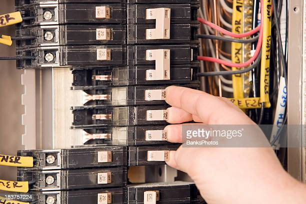 Electrician's Hand Turning On Circuit Breakers