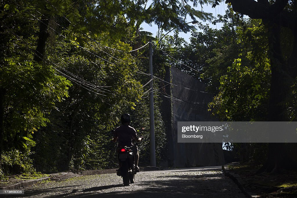 Electricity cables hang from a pole as a motorcyclist drives by in Rio de Janeiro, Brazil, on Monday, July 15, 2013. Energy developers in Brazil will bid for contracts to sell electricity Dec. 13 from plants due to go into operation in five years, including a 700-megawatt hydropower project in the Amazon. Photographer: Dado Galdieri/Bloomberg via Getty Images