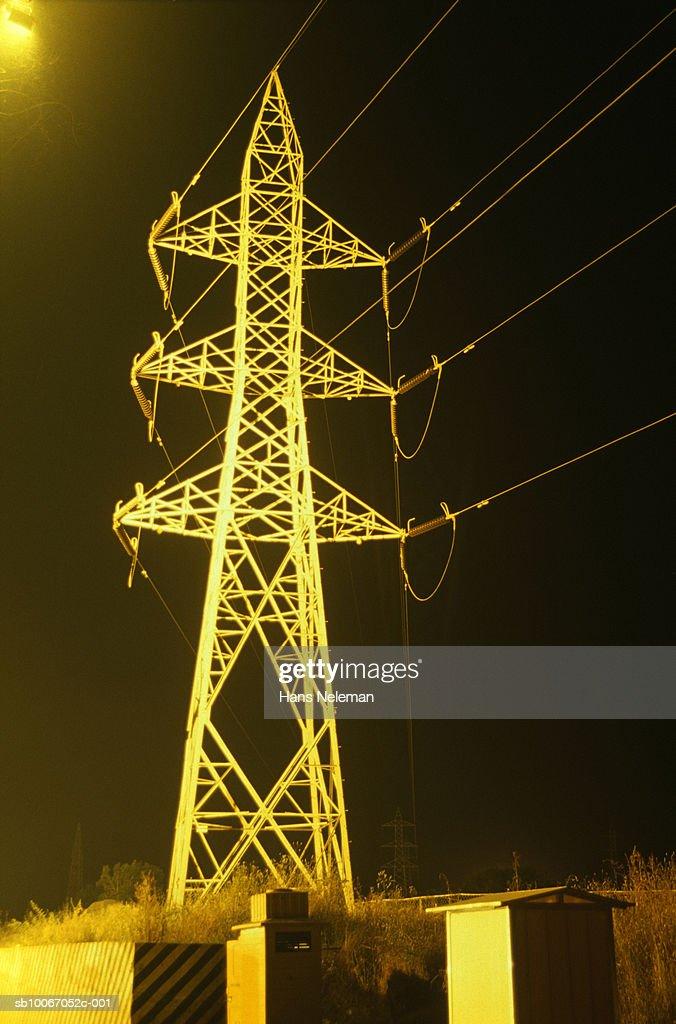 Electricity pylon by street, night : Stock Photo