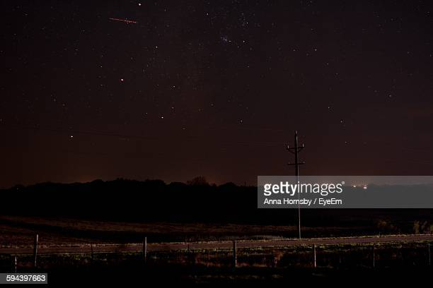 Electricity Pylon On Field Against Star Field At Night