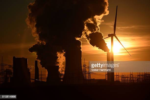 Electricity pylons and wind turbines stand beside the RWE Niederaussem coalfired power plant while Steam rises from cooling towers on February 16...