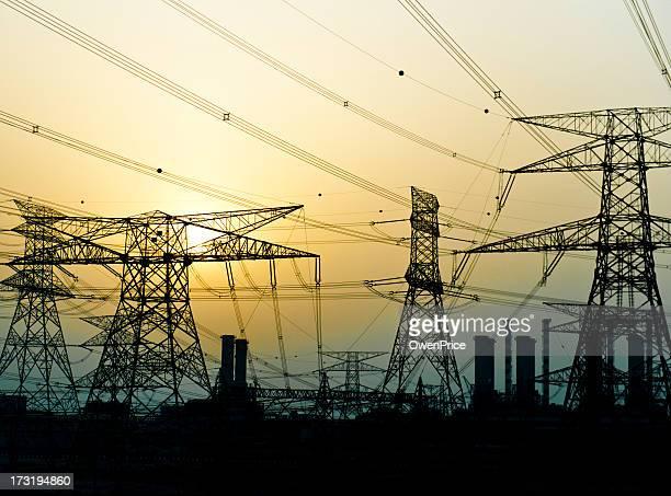 Pylônes électriques à proximité de power station au coucher du soleil