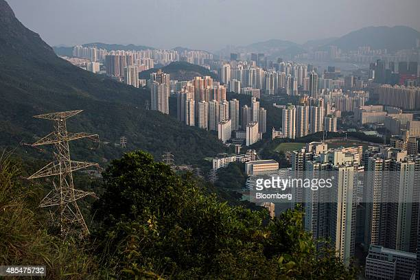 Electricity pylons on a hill stand near residential buildings in Hong Kong China on Tuesday Aug 25 2015 Prices of existing homes have risen 9 percent...
