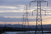 Electricity Pylons crossing a River into a Built up Area