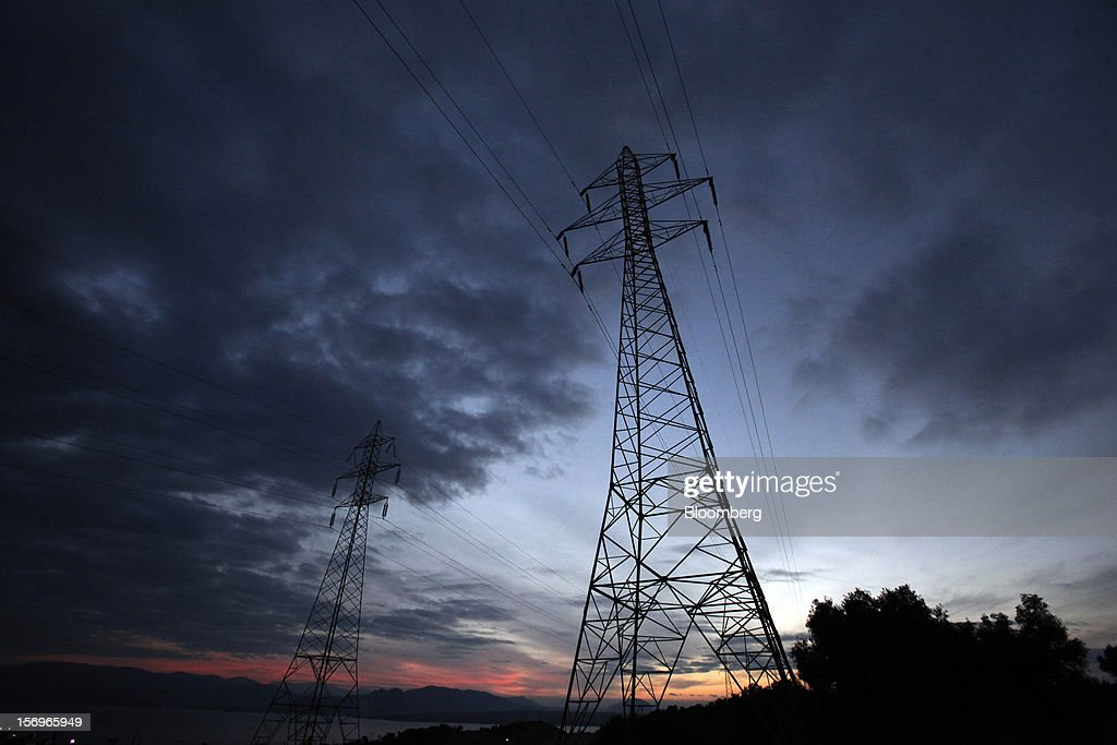 Electricity pylons stand silhouetted against the evening sun near the Motor Oil Hellas SA oil refinery in Agioi Theodoroi, Greece, on Friday, Nov. 23, 2012. Motor Oil Hellas SA Chief Financial Officer Petros Tzanetakis said Greek companies face difficulties in securing financing as foreign banks look at Greece with a 'skeptical eye.' Photographer: Kostas Tsironis/Bloomberg via Getty Images