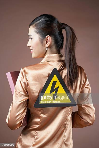 A Electricity sign on a businesswoman's back.