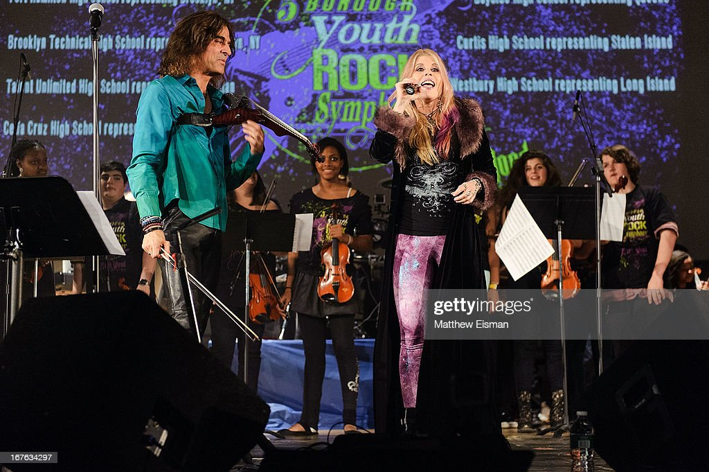 Electrify Your Music Foundation Founder/ electric violinist Mark Wood (L) and singer Laura Kaye perform live with The 5-Borough Youth Rock Symphony at the Electrify Your Music Foundation launch event at Brooklyn Technical High School Theater on April 26, 2013 in the Brooklyn borough of New York City.