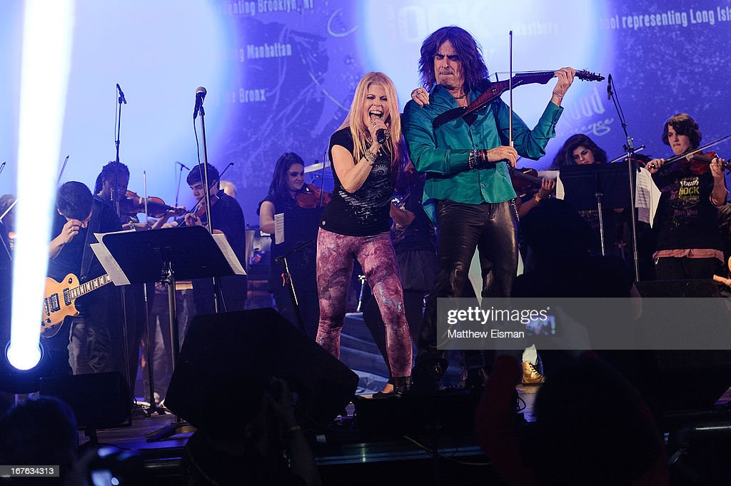 Electrify Your Music Foundation Founder/ electric violinist Mark Wood (R) and singer Laura Kaye perform live with The 5-Borough Youth Rock Symphony at the Electrify Your Music Foundation launch event at Brooklyn Technical High School Theater on April 26, 2013 in the Brooklyn borough of New York City.