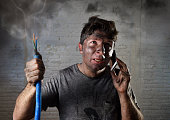 young man holding electrical cable smoking after electrical accident with dirty burnt face in funny desperate expression calling with mobile phone asking for help in electricity DIY repairs danger con