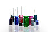 Electrolytic Capacitors, multi color and many sizes on white background, Double Exposure electronics part concept.